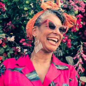 Designer Karen Arthur in pink dress laughing